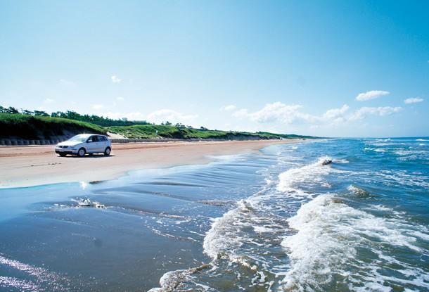 千里浜なぎさドライブウェイで海沿いを走る車